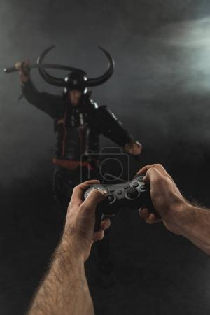 cropped shot of man controlling samurai character with gamepad on black