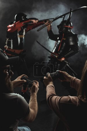 Photo for Back view of man and woman playing samurai fighting in real life with gamepads on black - Royalty Free Image