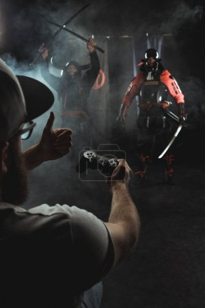 Photo pour Mature homme jouer samouraï combats avec gamepad dans la vie réelle et montrant pouce jusqu'à personnages - image libre de droit