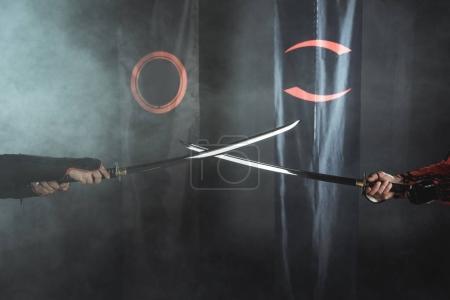 Photo pour Plan recadré de guerriers samouraïs croisant des épées de katana devant les symboles du clan - image libre de droit