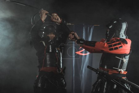 Photo for Armored samurai fighting with swords in front of clan symbols on flags - Royalty Free Image