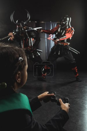 schoolchild playing samurai fighting with gamepad in real life
