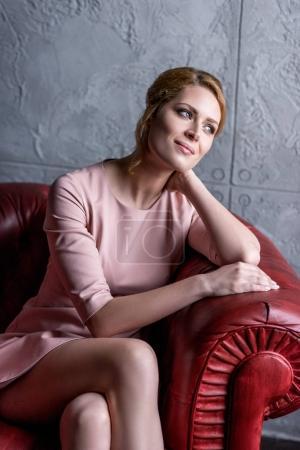Photo pour Réfléchie jeune femme en robe rose assise dans un fauteuil - image libre de droit