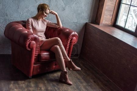 Photo pour Heureuse jeune femme en robe rose assise dans le fauteuil dans le grenier intérieur - image libre de droit