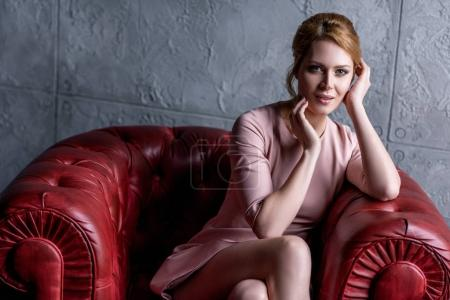 beautiful young woman in pink dress sitting in armchair and looking at camera