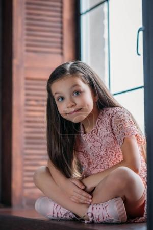 happy little child sitting on windowsill and looking at camera