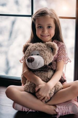 Photo for Happy little child sitting on windowsill with teddy bear - Royalty Free Image