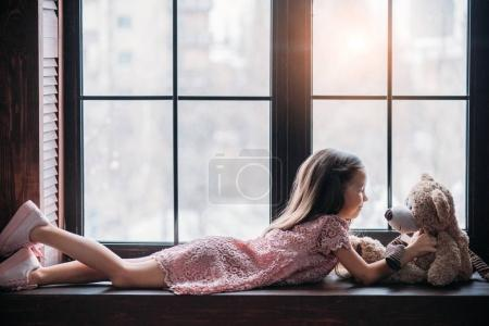 Photo pour Vue latérale du petit enfant jouant avec un ours en peluche allongé sur le rebord de la fenêtre - image libre de droit