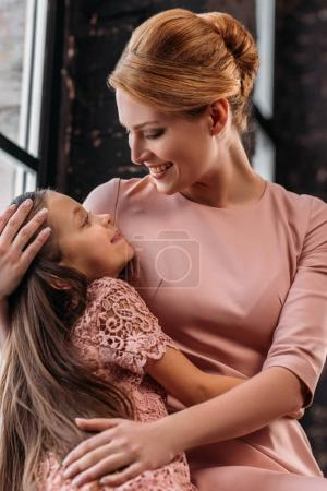 young beautiful mother embracing her little daughter