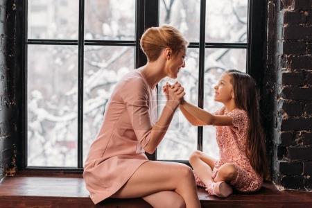 Photo pour Mère et fille assis sur le rebord de la fenêtre et parlant - image libre de droit