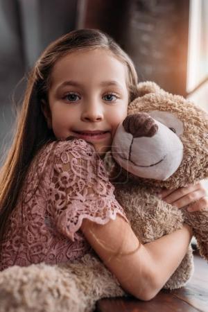 Foto de Feliz niño abrazando osito de peluche ond mirando a la cámara - Imagen libre de derechos