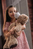adorable little child embracing teddy bear at home