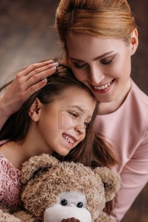 close-up shot of mother embracing her daughter while she holding teddy bear