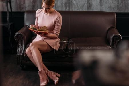 attractive young woman reading book on couch in loft interior