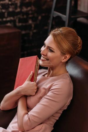 beautiful young woman embracing book while sitting on couch