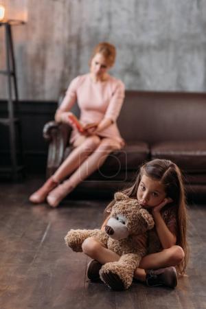 kleines depressives Kind sitzt mit Teddybär auf dem Boden, während ihre Mutter auf dem Sofa sitzt und Buch liest