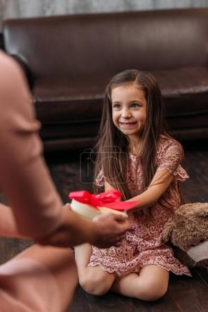 mother giving birthday gift to happy little daughter