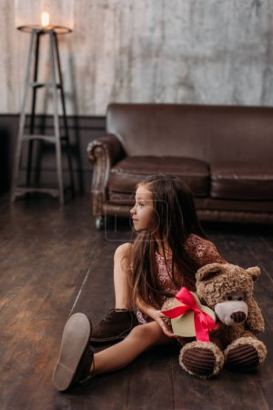 adorable little child with giftbox in shape of heart and teddy bear sitting on floor