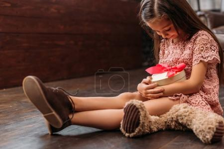 adorable little child holding giftbox in shape of heart while sitting on floor