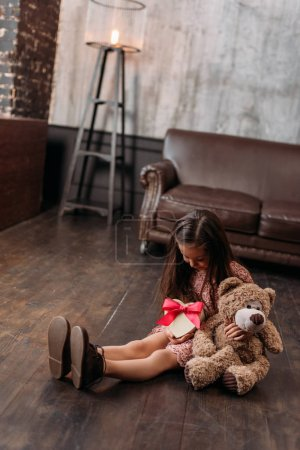 little child holding giftbox in shape of heart while sitting on floor
