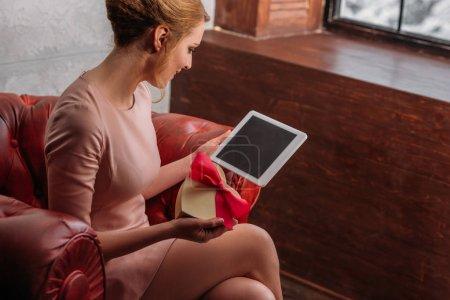 Photo pour Heureuse jeune femme avec cadeau de Saint-Valentin et tablette - image libre de droit