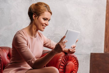smiling young woman in dress using tablet while sitting in armchair