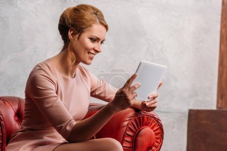 Photo pour Souriant jeune femme en robe en utilisant la tablette tout en étant assis dans le fauteuil - image libre de droit
