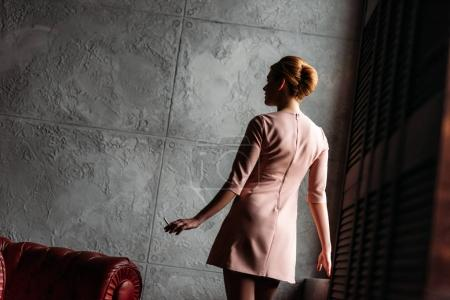attractive young woman in dress in front of concrete wall