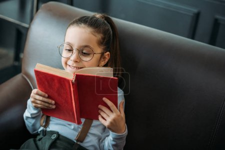 happy little child reading book on couch at home