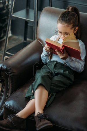 high angle view of adorable little child reading book on couch at home