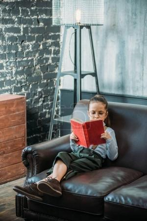 concentrated little child reading book on couch at home