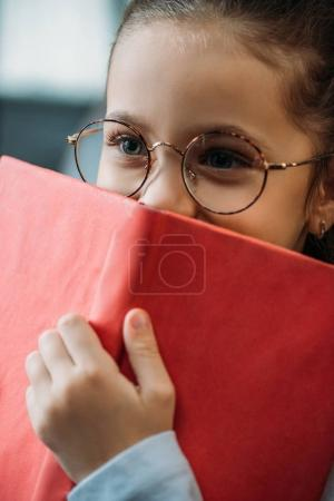 close-up portrait of adorable little child covering face with red book