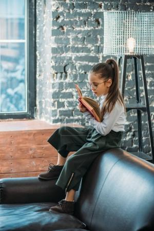 focused little child reading book while sitting on couch in loft apartments