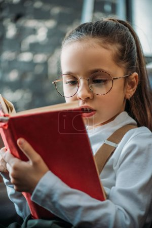 close-up portrait of concentrated little child reading book