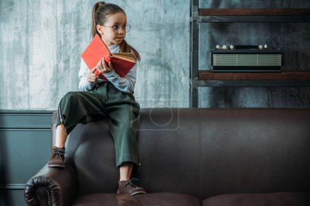thoughtful little child with book sitting on couch in loft apartments