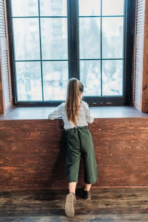 back view of little child in stylish clothing standing at window