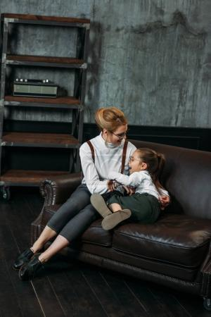mother and daughter embracing on couch in loft apartments