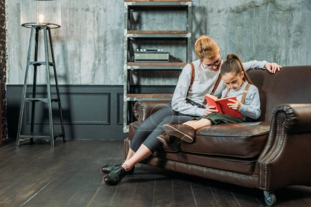 mother and daughter reading book together on couch
