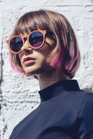 portrait of stylish girl with pink hair and sunglasses looking away