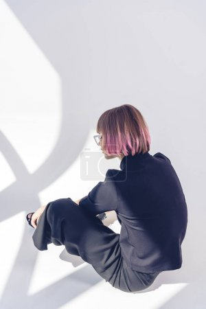 Photo for Rear view of stylish girl sitting in black clothes on white - Royalty Free Image