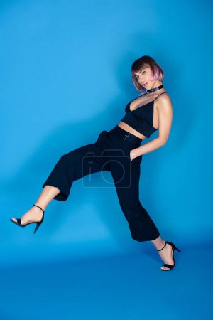 beautiful fashionable girl posing with leg up on blue