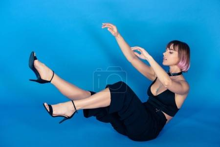 stylish girl in crop top falling isolated on blue