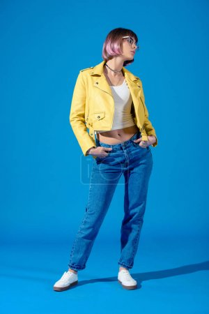 stylish girl posing in jeans and leather jacket on blue