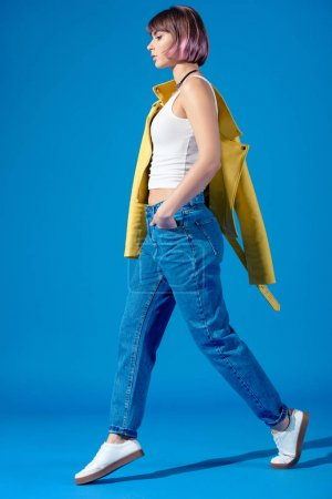 side view of stylish girl walking on blue