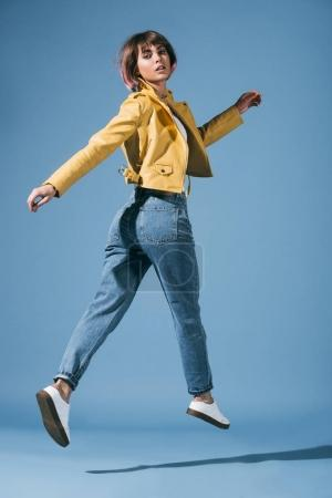 stylish girl jumping and looking at camera on blue