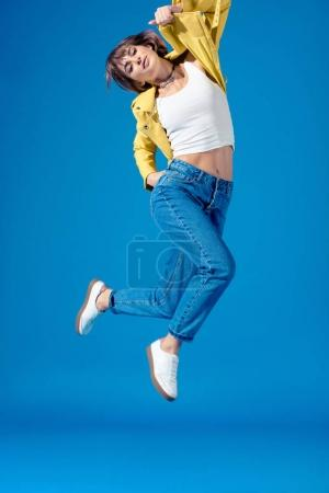 girl in stylish clothes jumping isolated on blue
