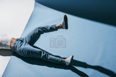 cropped image of stylish girl lying on floor in jeans with one leg raised