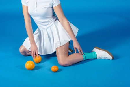 Cropped image of sexy sportswoman sitting with oranges and mandarin on blue