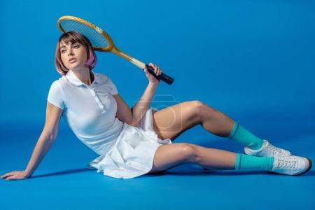Photo for Sexy Tennis player sitting with tennis racket and looking away on blue - Royalty Free Image