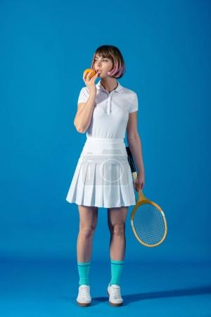 tennis player standing with orange and tennis racket on blue